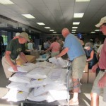 Volunteers moving 50 pound bags of rice into position for packing meals.